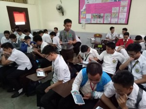 Teacher Jimrey Dapin supervises his junior high students as they use tablets during a classroom activity which utilizes mobile applications.