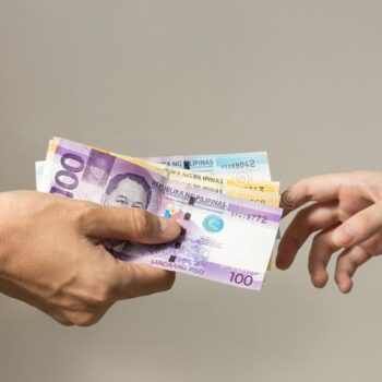 hand-holding-giving-cash-banknotes-philippines-peso-paying bills payment procedure hand holding giving cash
